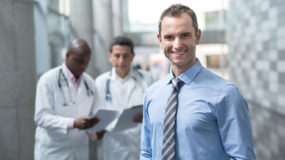 Businessman with online healthcare administration degree smiles in hospital